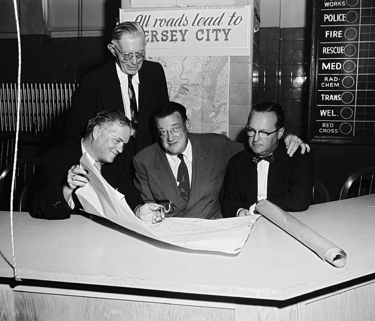 shown  with Jersey City officials, announced that, in 1956 through 1958, the Dodgers would play seven games each season in Jersey City and would have the option to continue the agreement for three years beyond that.