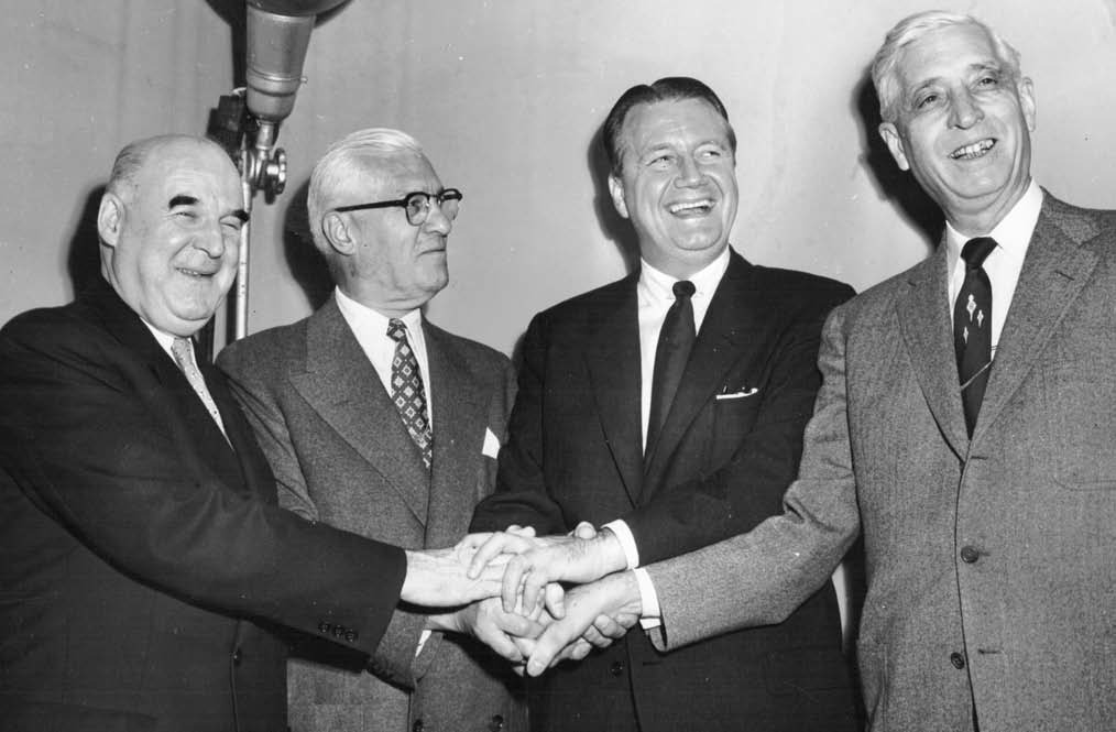 Handshakes and smiles are all around as Arnold Johnson and his allies celebrate after league owners agreed to the sale and relocation of the A's to Kansas City on November 8, 1954. From left: Roy Mack, league president William Harridge, Arnold Johnson, and Kansas City mayor William E. Kemp.