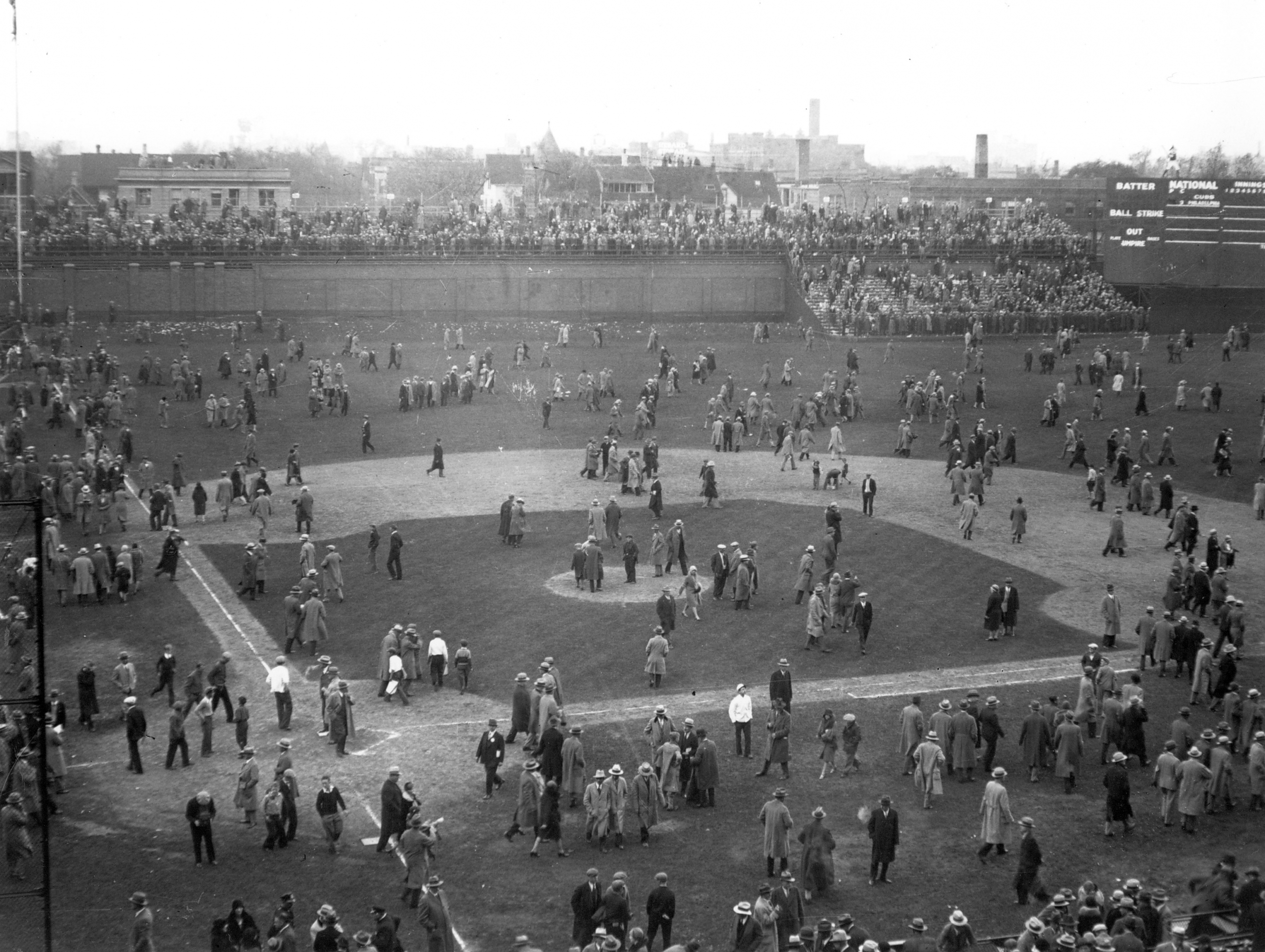 "Fans depart Wrigley Field via the diamond. Note the temporary bleachers set up beyond the left field wall on Waveland Avenue as well as the ""jury box"" section in left-center field."